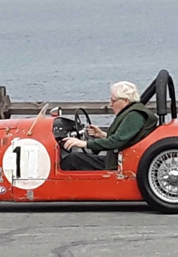 Older gentleman driving a restored red race car near the ocean