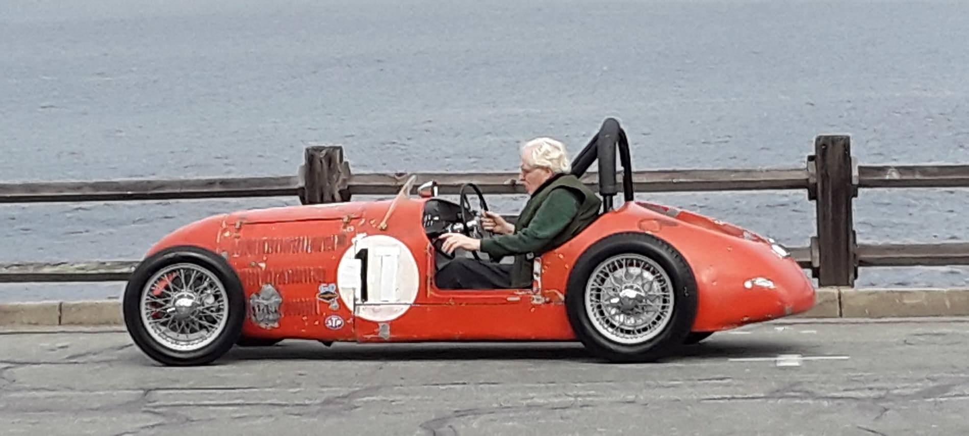 Older gentleman driving a restored red race car near the ocean