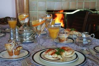 Table set with breakfast egg dish on plates and orange juice in glasses