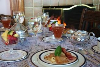 Table set with breakfast crepes on white plate with fruit cup in glass dish and apple juice