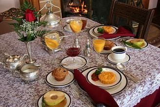 Table set with breakfast egg dish on white plate with muffin, orange juice, and coffee on the side