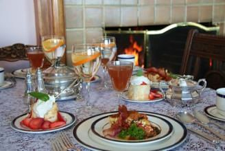 Table set with breakfast tomato tart dish on white plate with strawberry shortcake and apple juice on the side