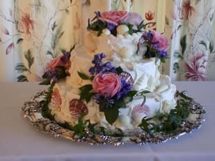 Three tiered white wedding cake with seashells and purple and pink flowers on a round silver tray