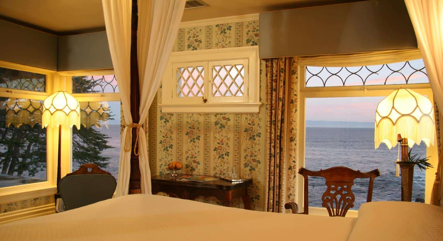 Guest room with several windows overlooking the Bay, floral walls, and white canopy bed