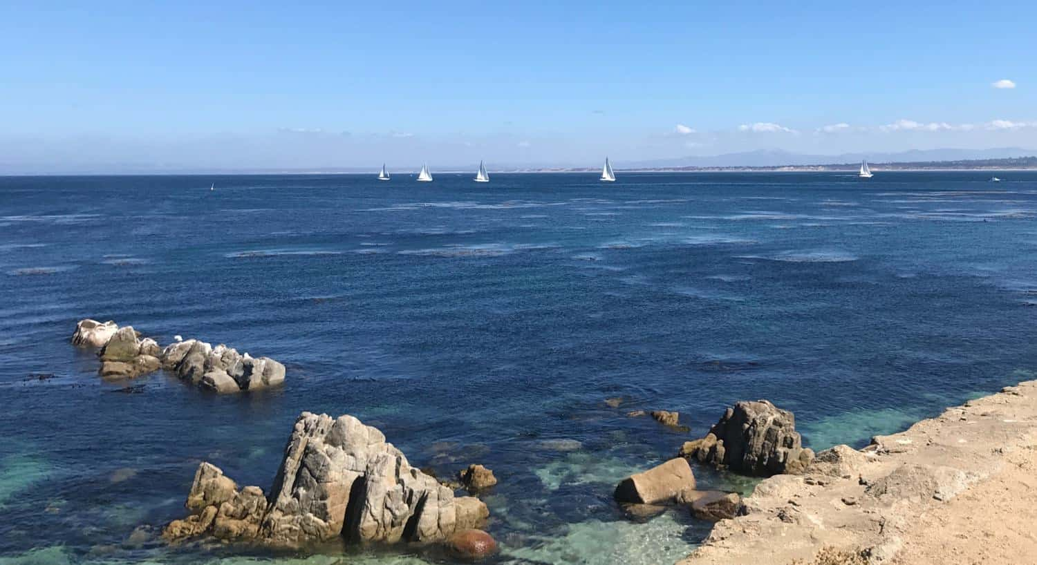 Blue Pacific ocean with white sailboats in the distance and a rocky shoreline
