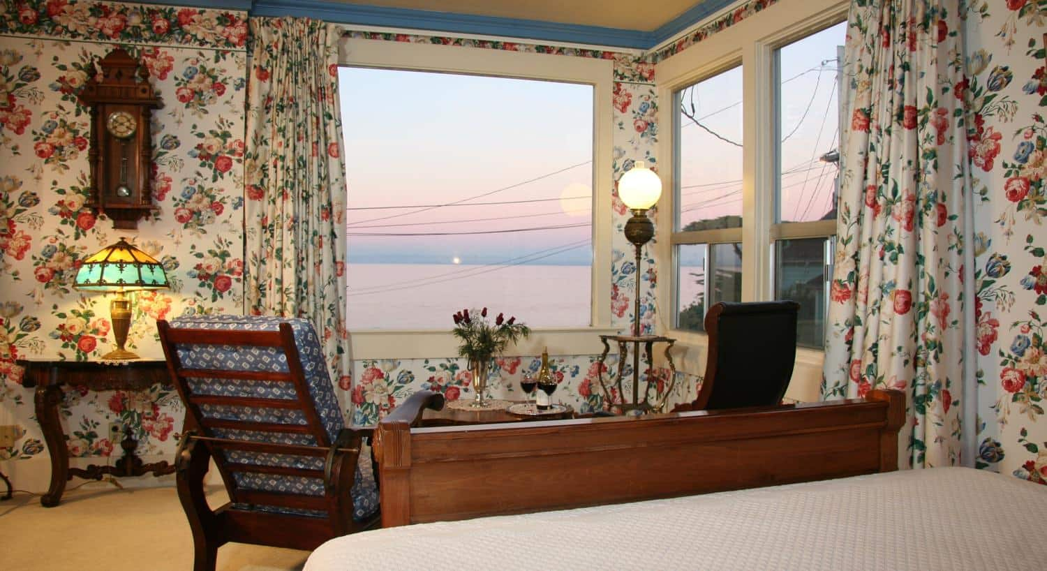 Corner guest room with ocean views, floral walls, sitting chairs and bed with white bedding