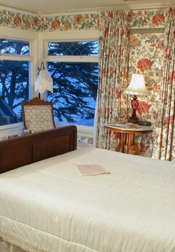 Corner guest room with floral walls, ocean views, dresser with mirror and bed with white bedding