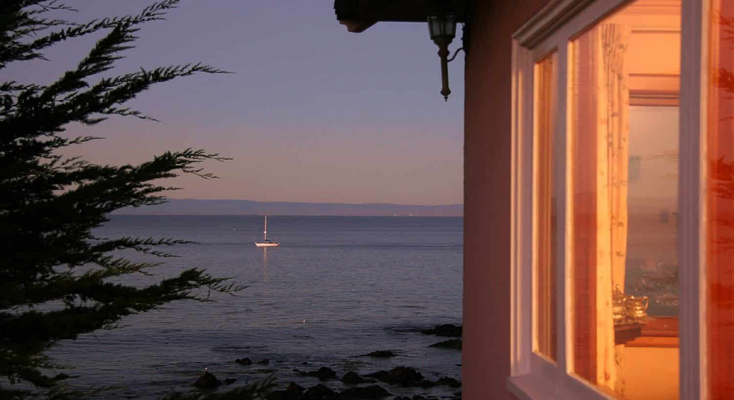 Ocean view outside the inn after sunset with single sailboat