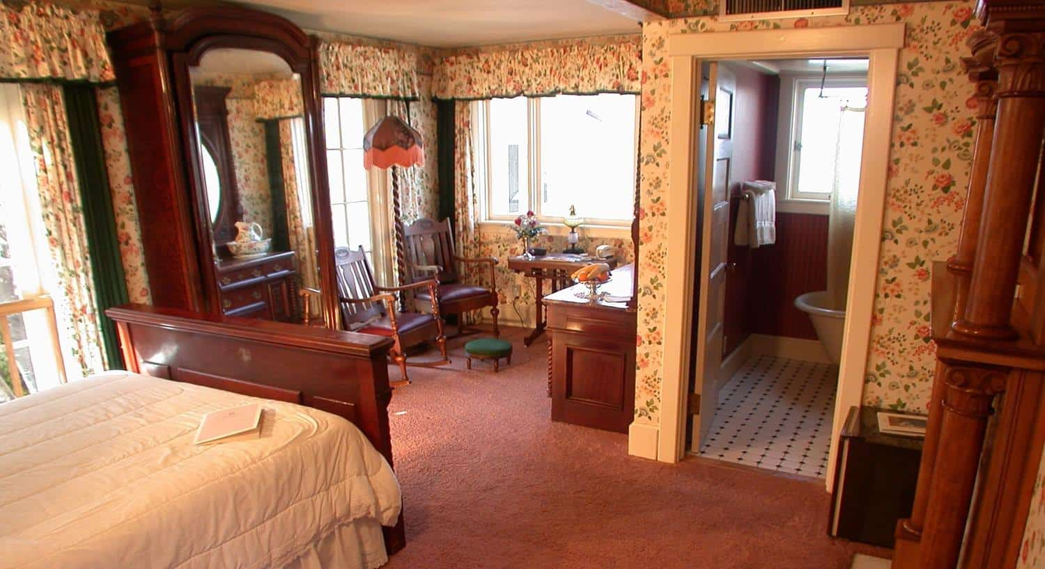Guest room with several windows, floral walls, wood bed, white bedding, attached bath