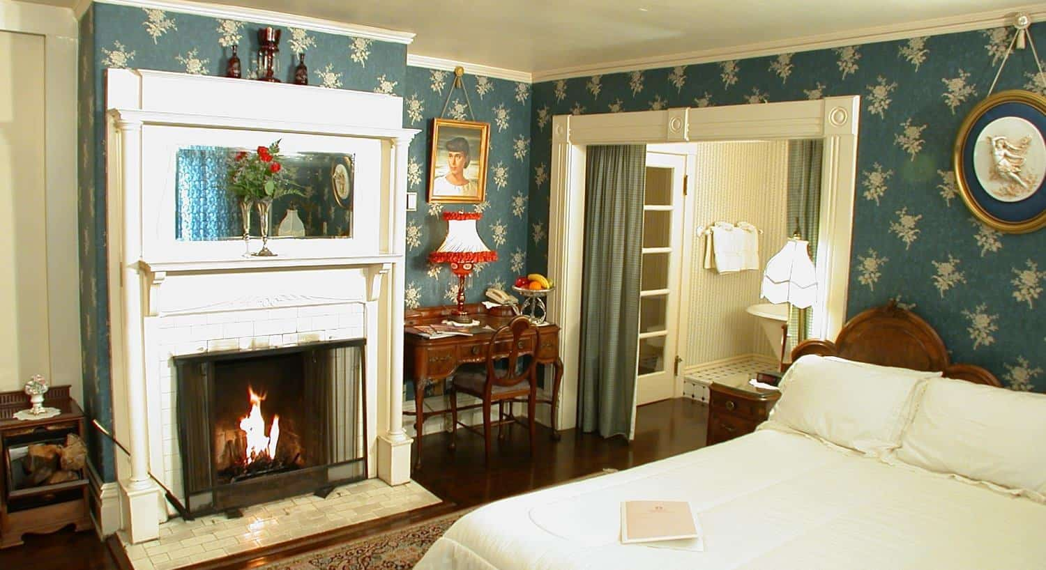 Guest room with blue-green walls, fireplace with white painted wood surround and bed with white bedding