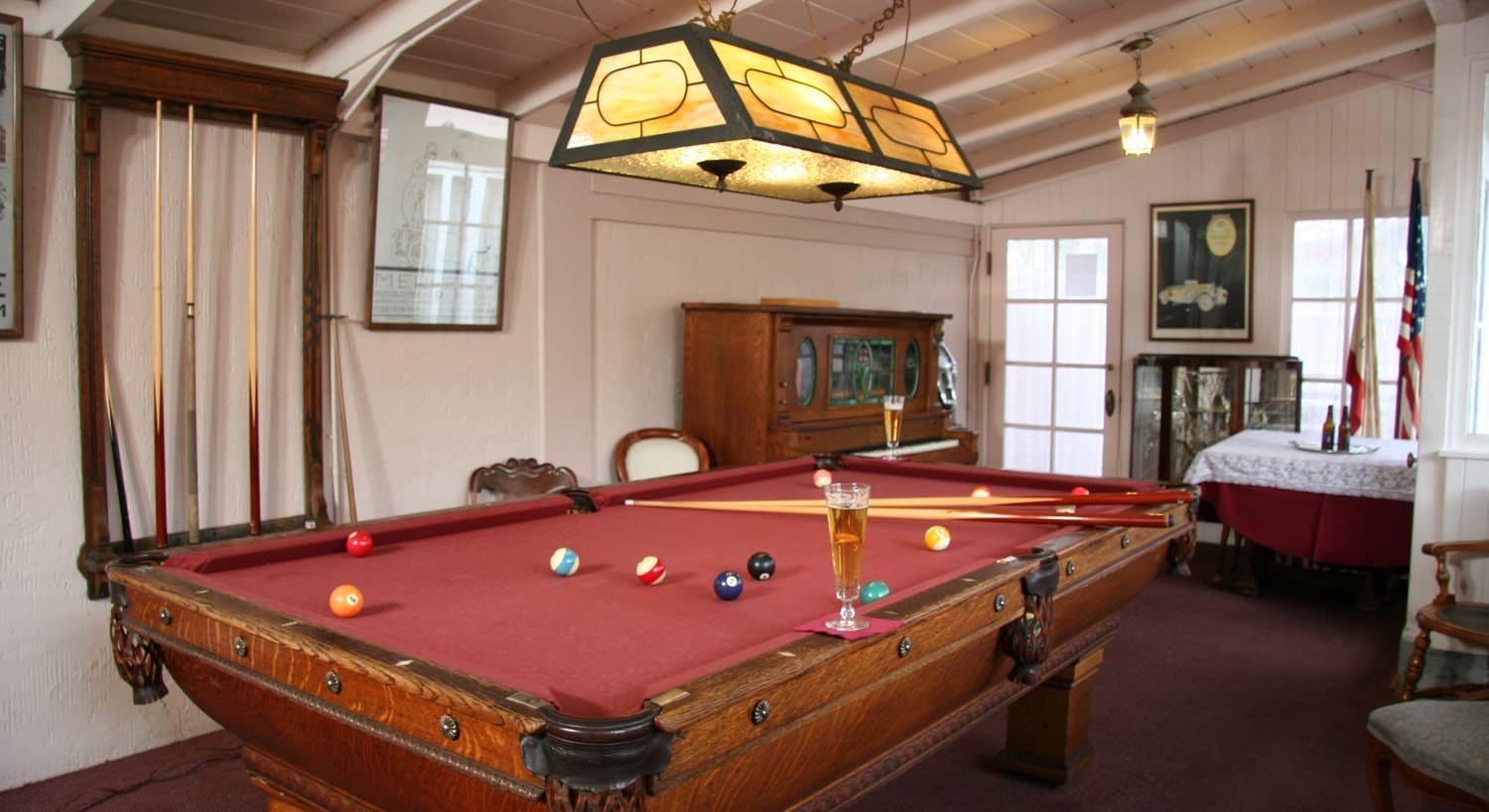 Common room with pool table with red felt and topped with balls and cue sticks, and several windows
