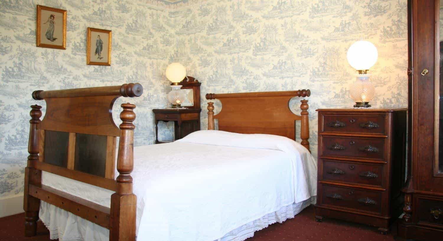 American guest room with blue papered walls, wooden bed, nightstand and small chest with lamps and wood armoire
