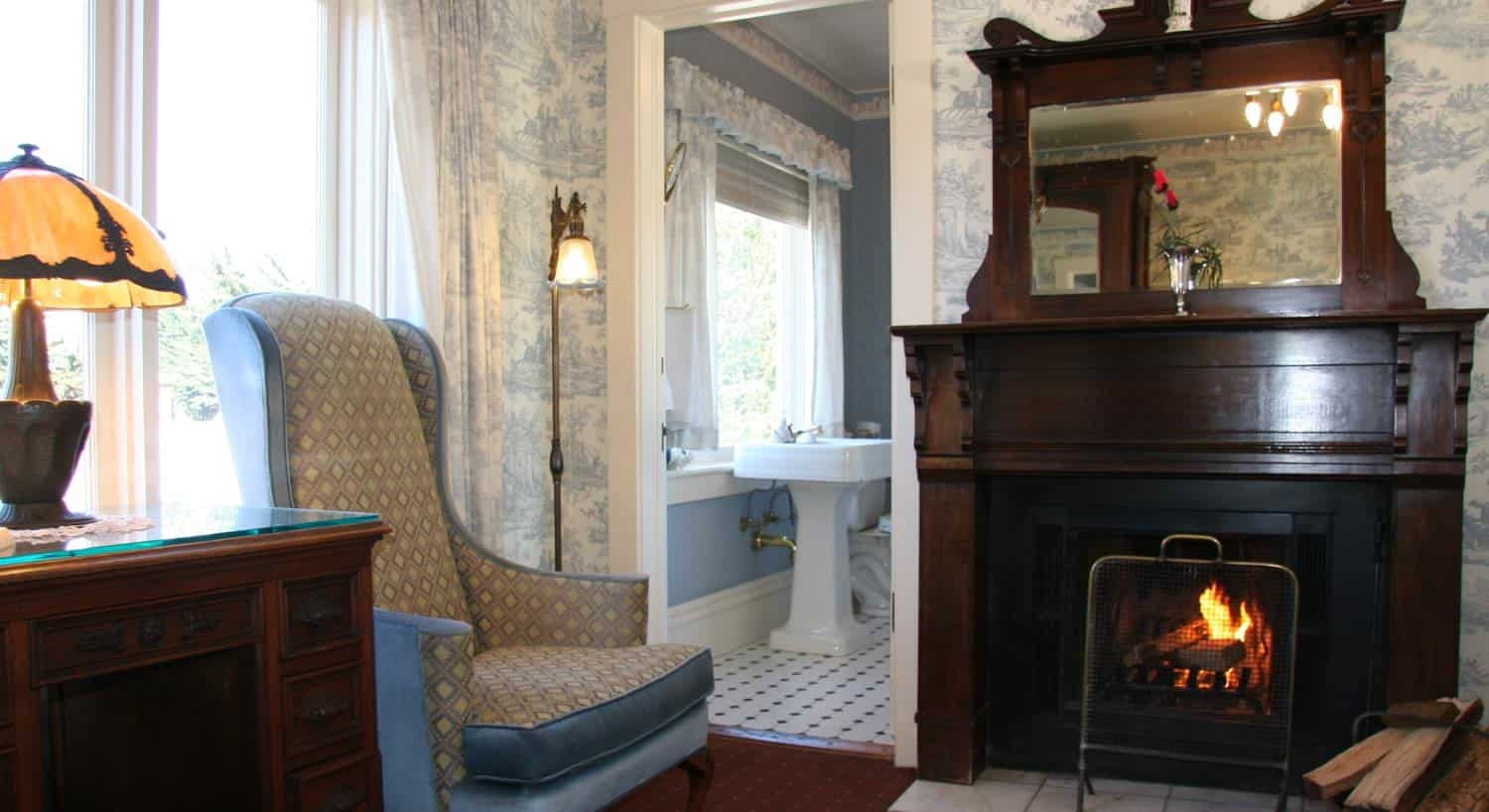 American guest room with blue papered walls, fireplace with wood mantel surround, upholstered chair, desk, large window and attached bath