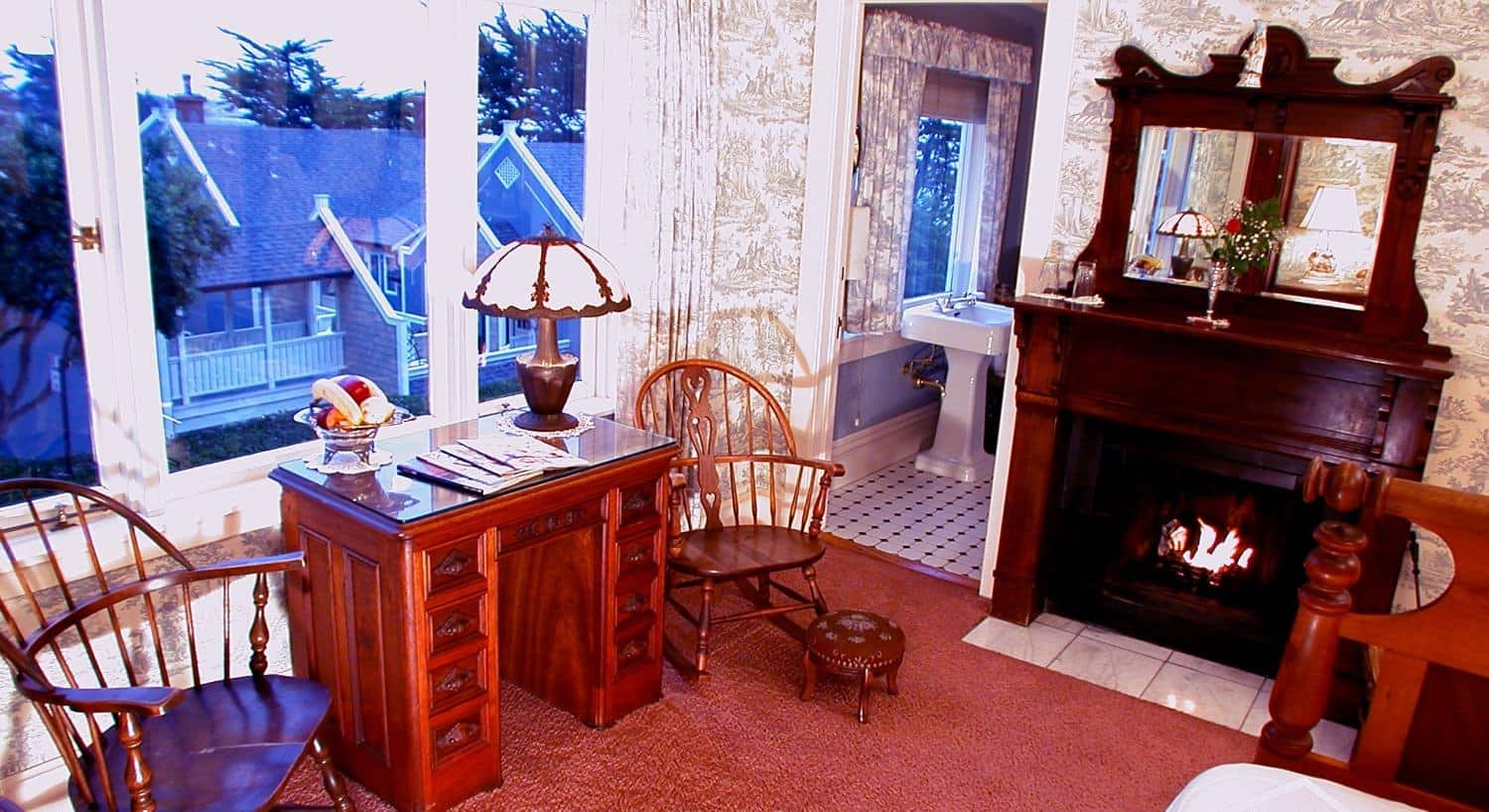 American guest room with triple window, carpeting, fireplace with warm fire, desk, chairs and attached bathroom