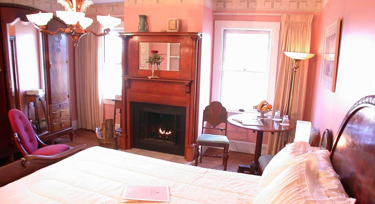 Art Deco guest room with pink walls, two windows flanking a fireplace, armoire, several chairs and bed with white bedding