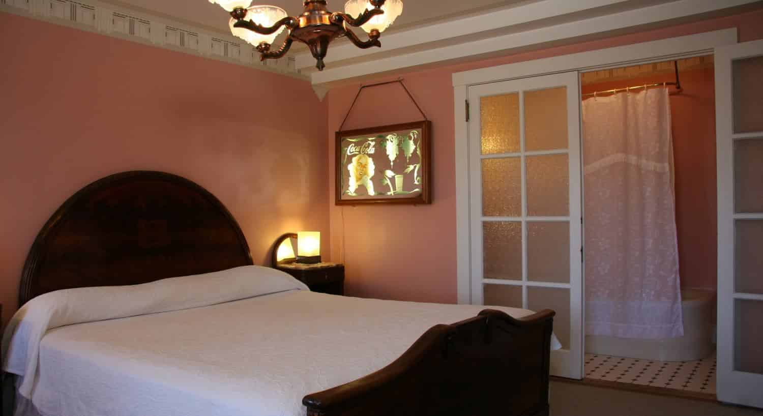 Art Deco guest room with pink walls, glass French doors, and wood bed with white bedding