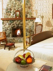 Brass guest room with floral papered walls, carpeting, wood bed with brass canopy, stone fireplace and wood armoire