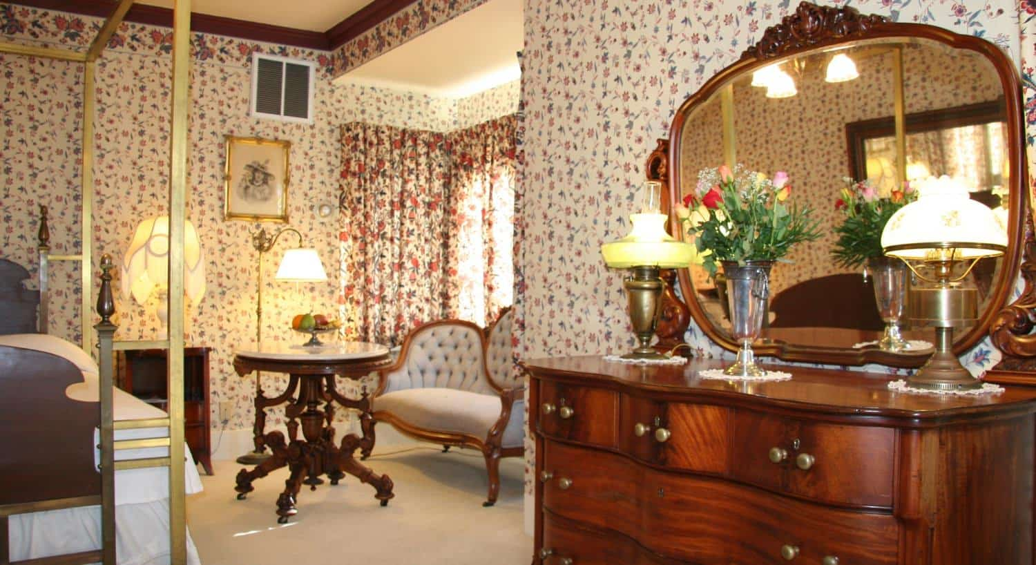 Brass guest room with floral walls, wood bed with gold canopy, dresser with mirror, fresh flowers and sitting area with windows
