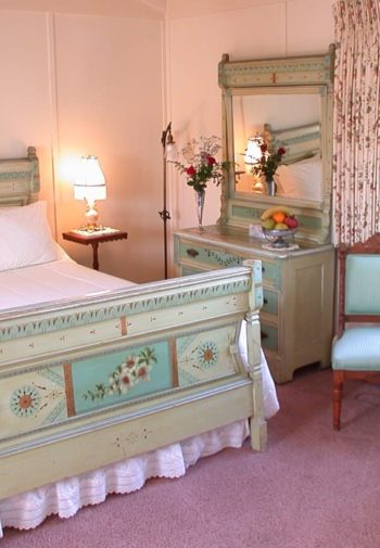 California guest room with carpeting, two chairs and round table in front of a window, painted bed and dresser