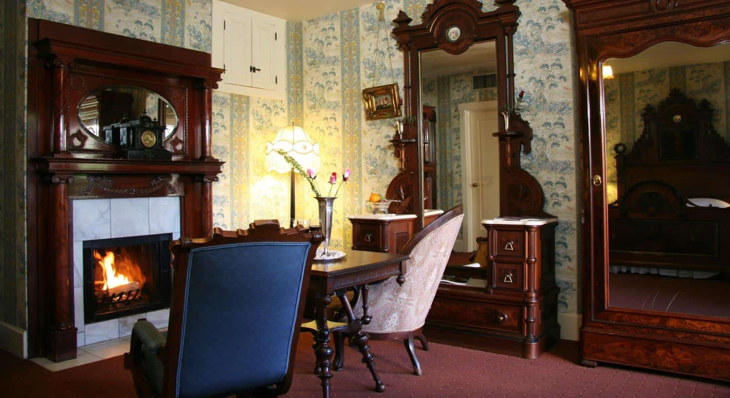 Captains guest room, floral and striped wallpaper, carpeting, carved wood furniture, fireplace with wood surround