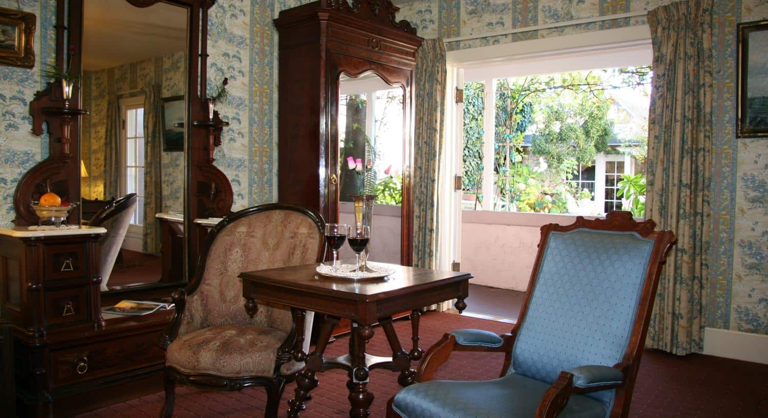 Captains guest room, carpeting, large window, papered walls, floral curtains, vanity with mirror, armoire with mirror, two chairs, square table