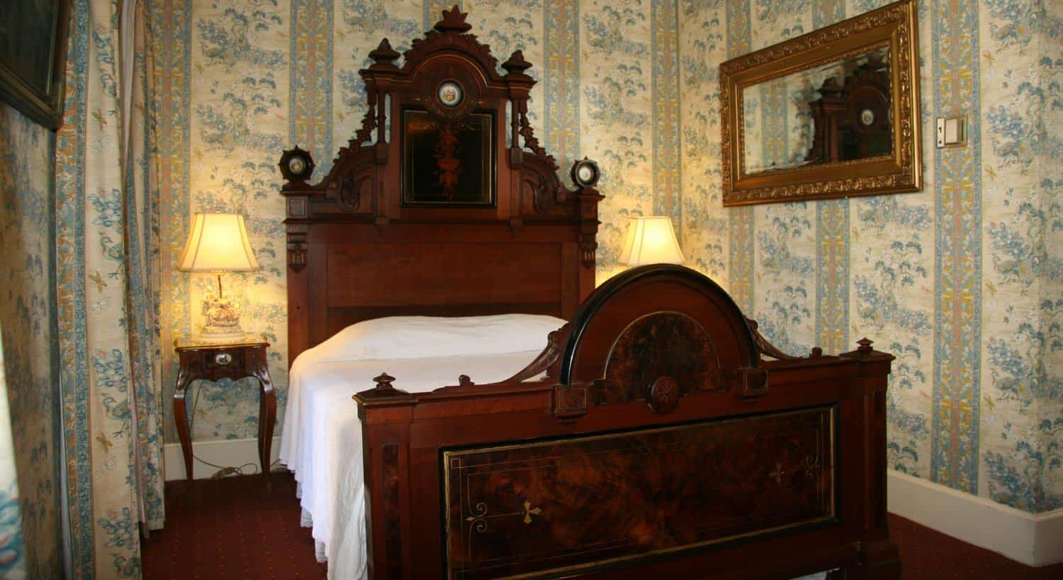 Captains guest room, blue floral and striped walls, carved wooden bed with tall headboard, two nightstands with lamps