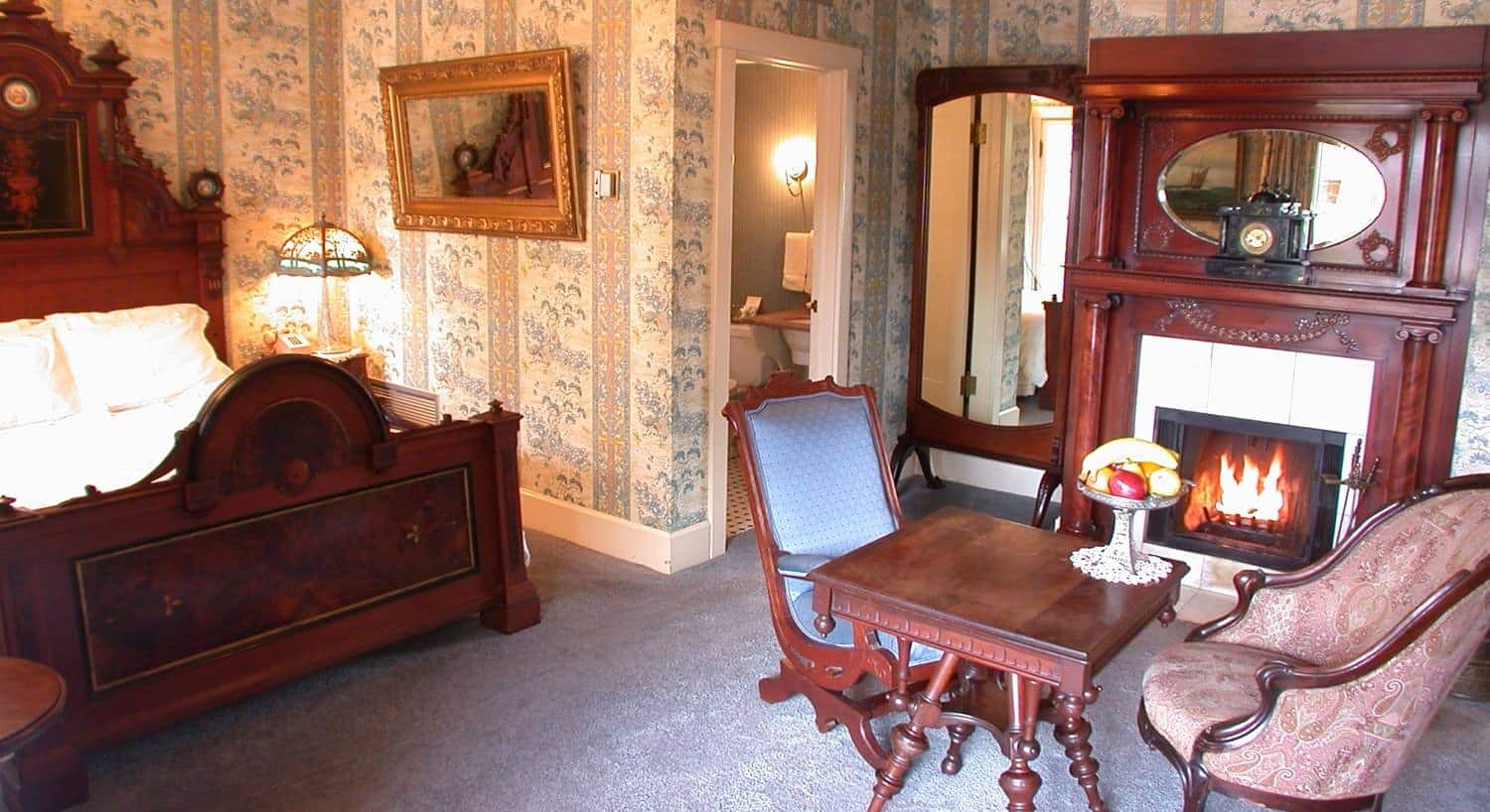 Captains guest room, pink and blue floral and striped walls, carved bed with tall headboard, fireplace. two chairs, square table