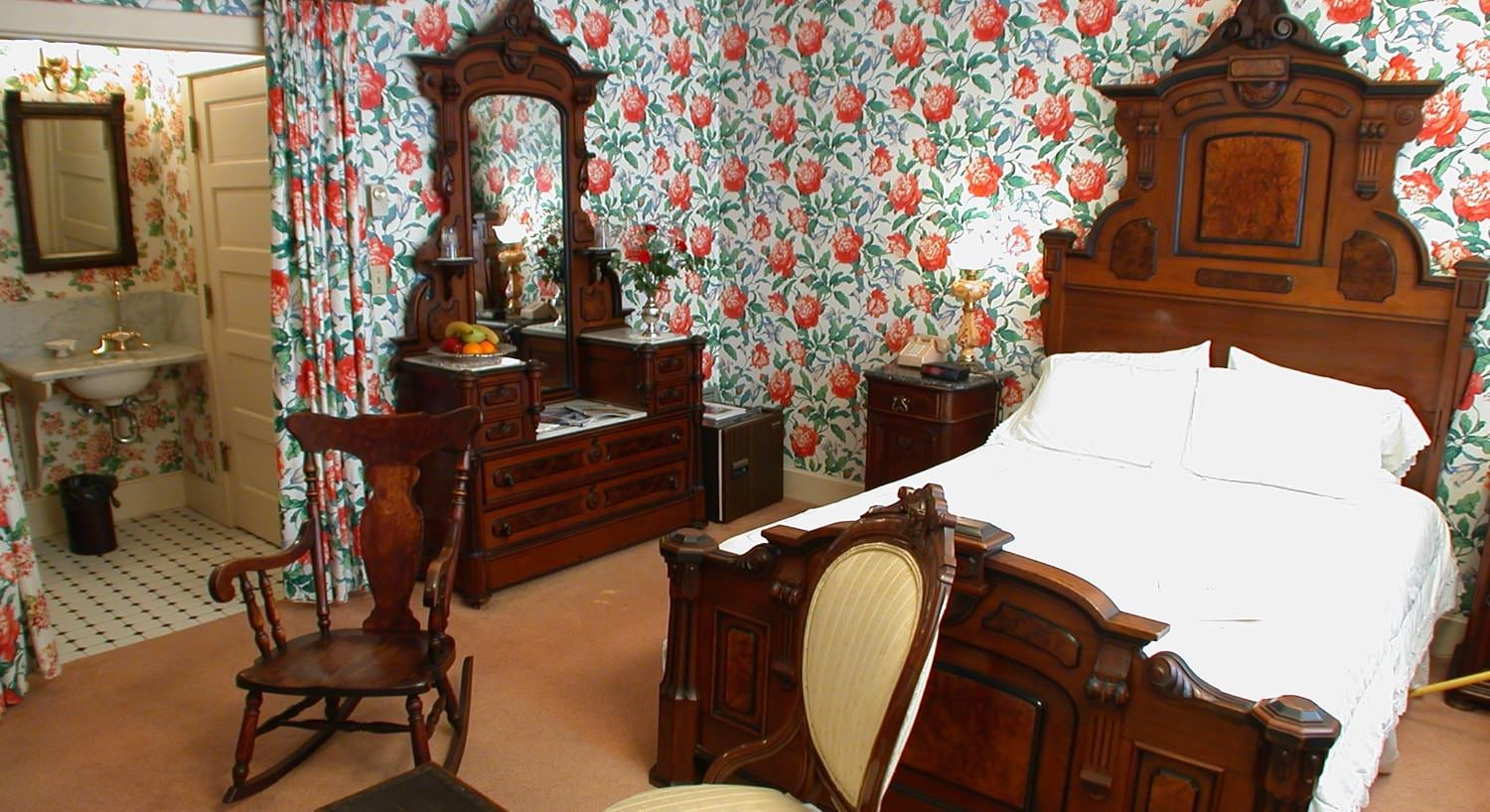 Carriage guest room with red and green papered walls, carpeting, carved wooden bed, elegant vanity dresser with mirror, and rocking chair
