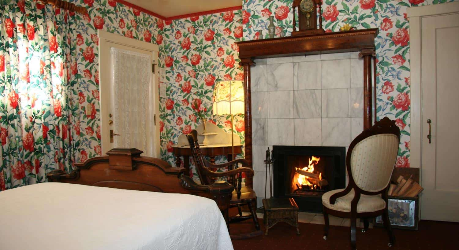 Carriage guest room with floral papered walls, two chairs in front of a fireplace, and floral curtains