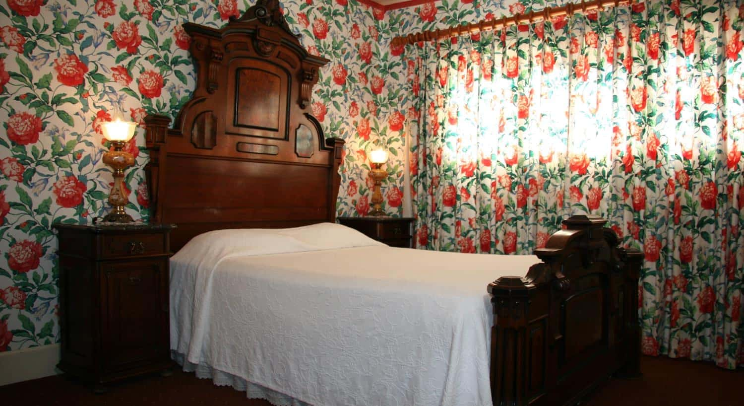 Carriage guest room with carved wood bed, tall headboard, two nightstands, red and green floral walls and curtains