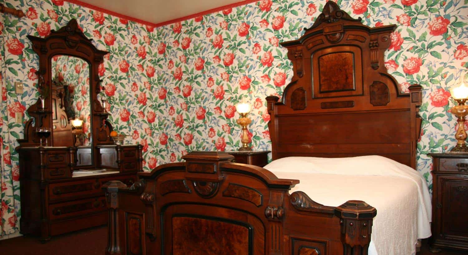 Carriage guest room with carved wood bed, tall headboard, two nightstands, red and green floral walls and vanity dresser