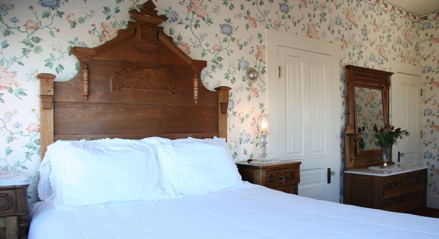 Cottage guest room with pastel floral walls, tall, wooden carved headboard, nightstands and dresser with mirror