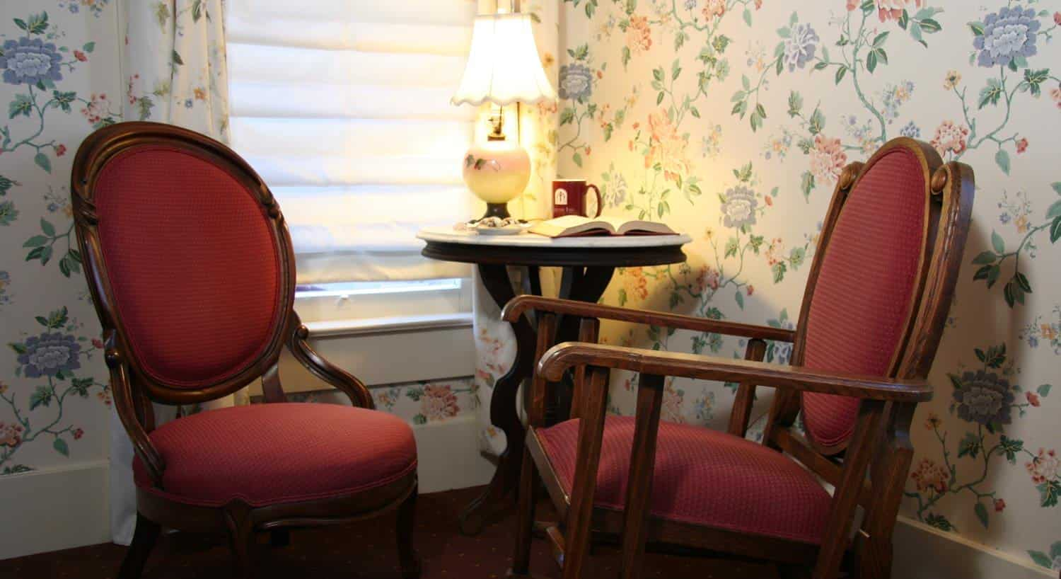 Cottage guest room with pastel floral walls, and two red chairs and small round table by a window
