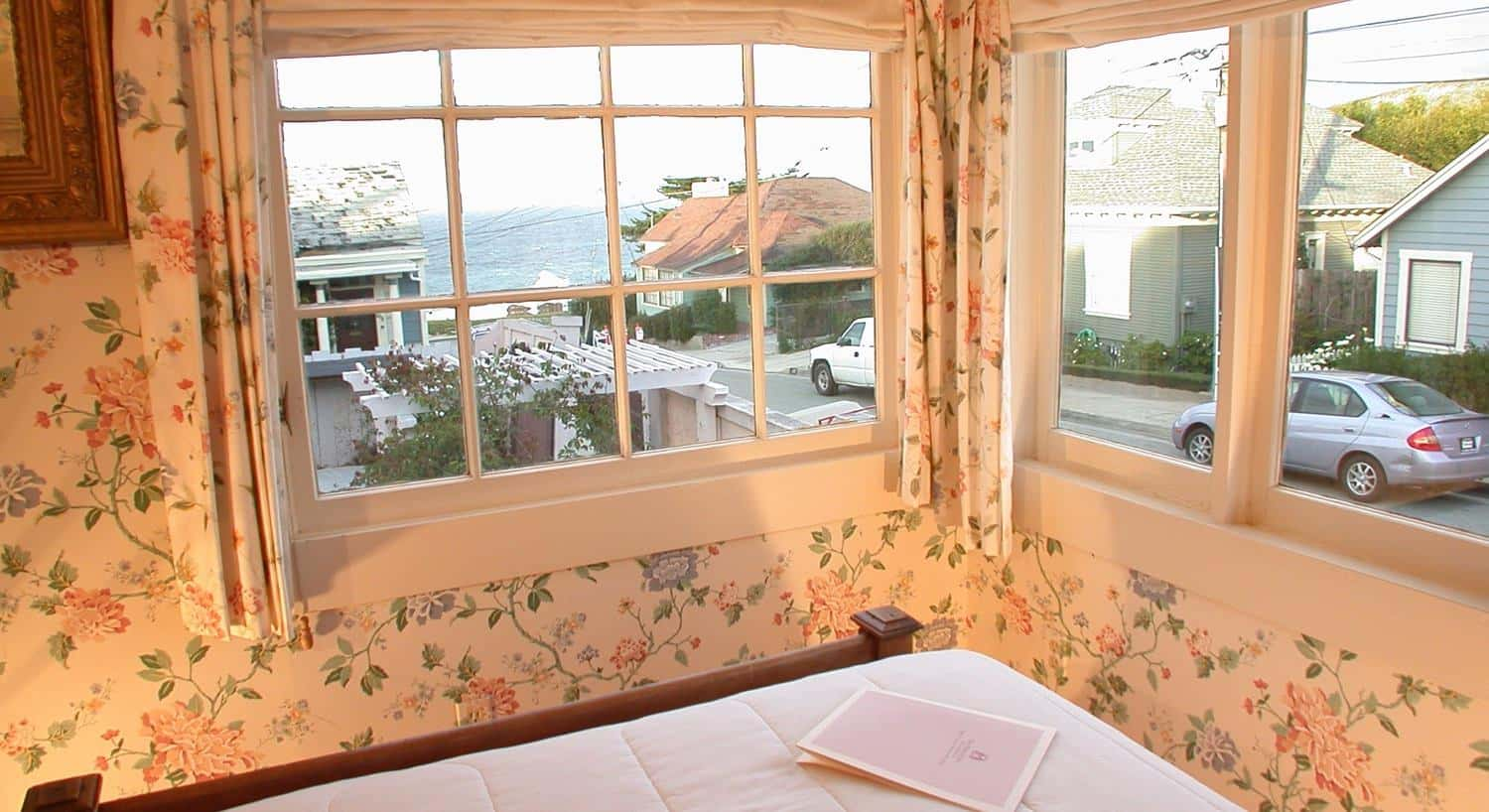 Cottage guest room with corner windows, ocean views, and floral walls