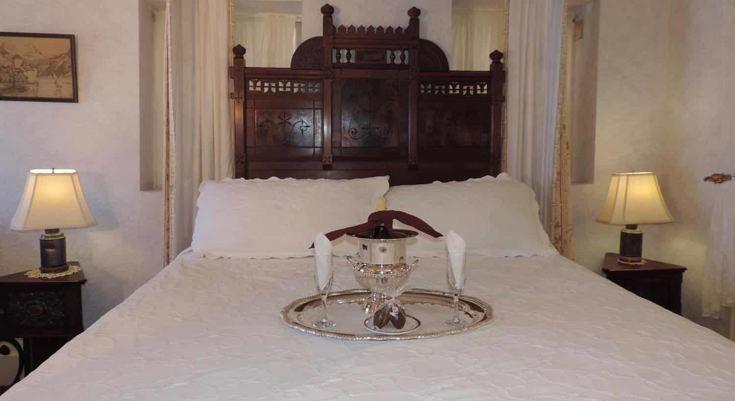 Eastlake's guest bed with tall, wood, carved headboard, white bedding, matching nightstands, and chilled champagne on the bed