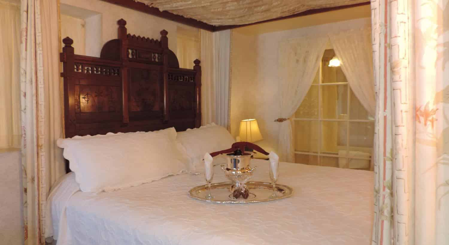 Eastlake guest room's canopy bed with carved wood headboard, white bedding, and champagne chilling on the bed