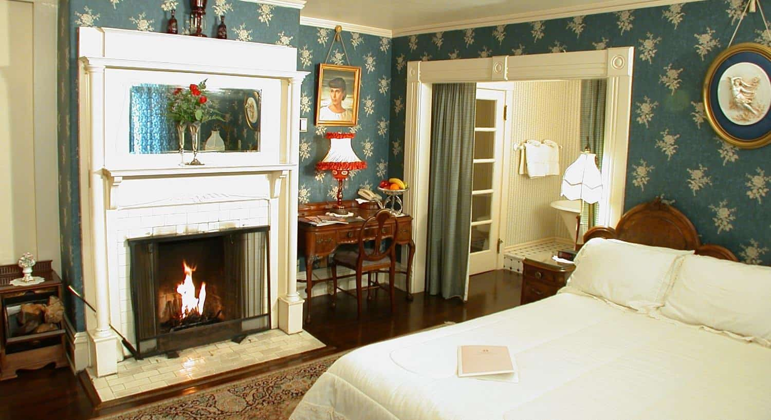 Edith guest room with blue-green papered walls, fireplace with white painted wood surround, and wood bed with white bedding