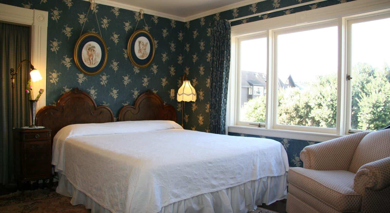 Edith guest room with blue-green papered walls, triple window, upholstered chair and wood bed with white bedding