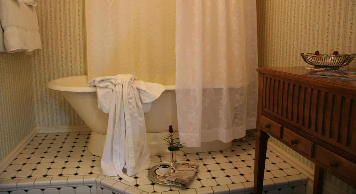 Edith guest bath with white freestanding tub, white shower curtain and wood vanity