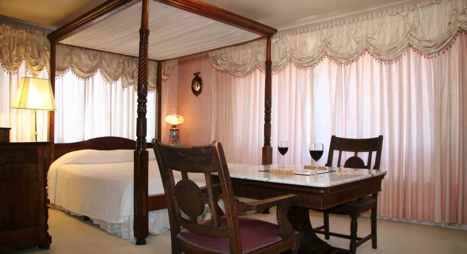 Empire guest room with several windows covered in pink sheers, wood four poster bed, marble-top table with two chairs