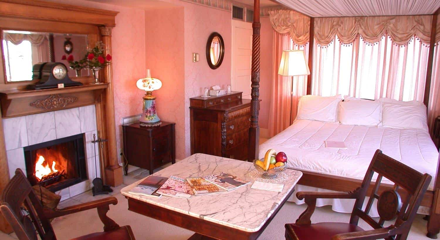 Empire guest room with pink walls, four poster canopy bed, marble-top table with two chairs and fireplace