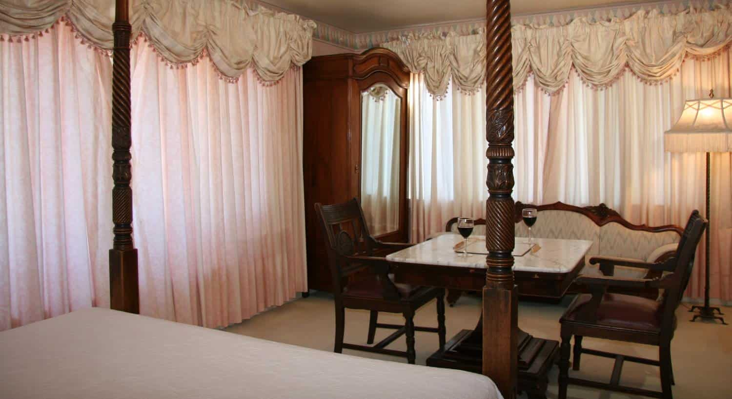 Empire guest room with pink sheer curtains, armoire with mirror, marble-top table with two chairs, settee and canopy bed