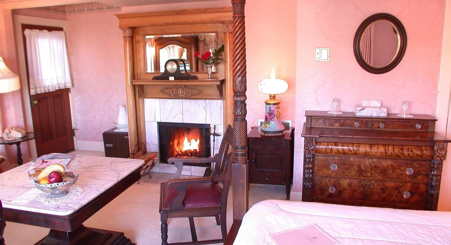 Empire guest room with pink walls, fireplace, marble topped table with chairs and dresser