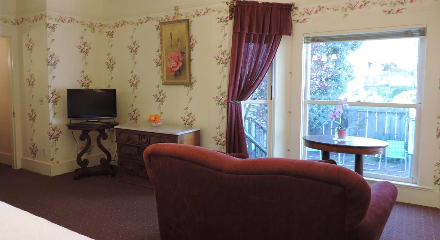 Guest room with ivory floral papered walls, large window, upholstered chair, several tables and a TV