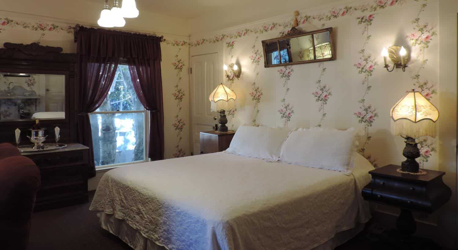 Guest room with ivory floral papered walls, window with eggplant colored curtains, and nightstands with lamps