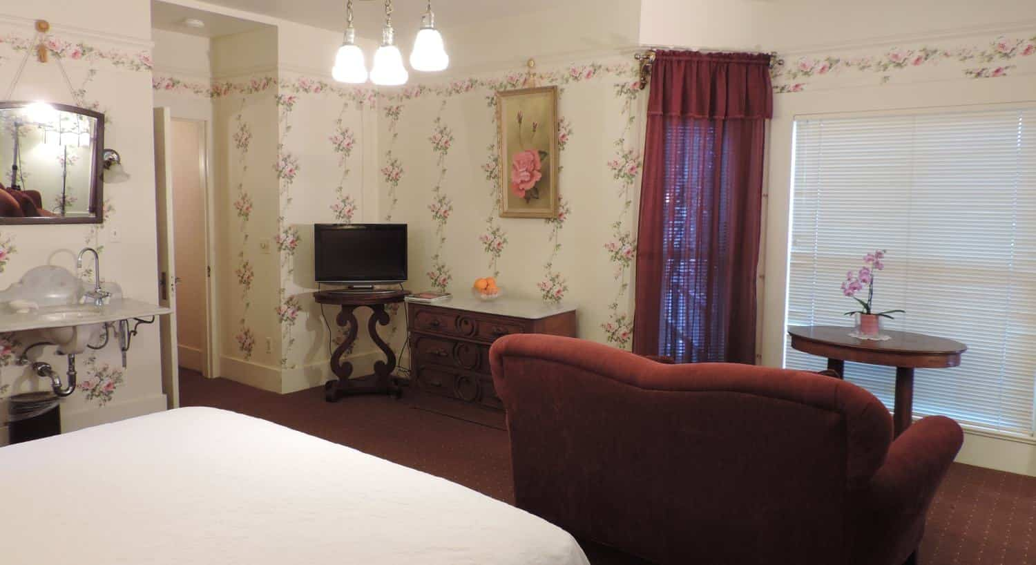 Guest room with ivory floral papered walls, carpeting, guest bed, wash basin, and upholstered chair with table