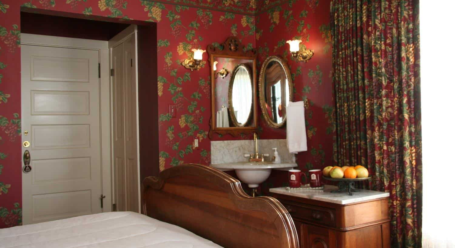 Fountain guest room with red floral walls, wood bed, corner wash basin and small table with mugs and apples