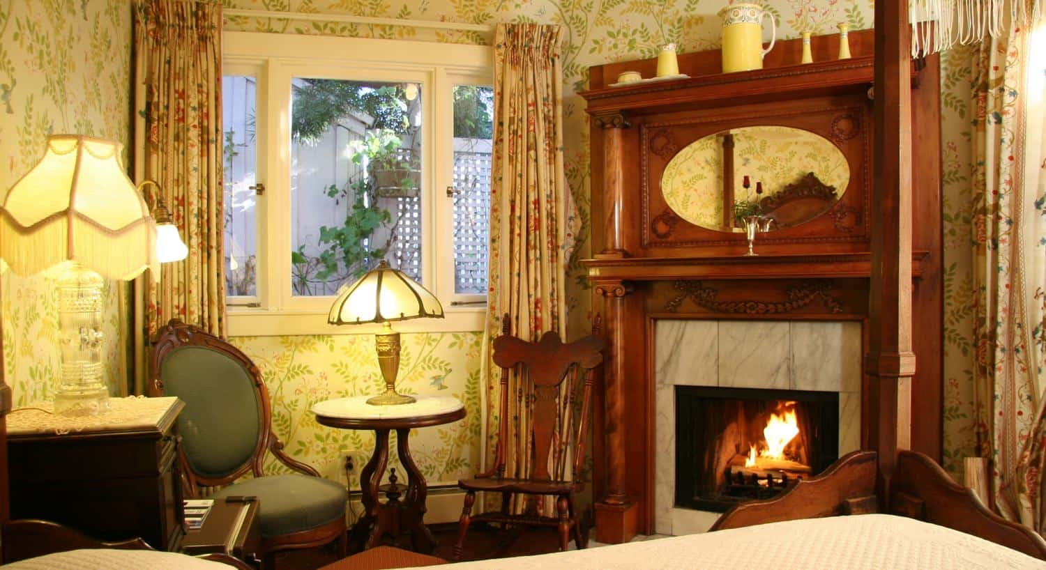 Garden guest room with leafy printed wallpaper, corner fireplace with surrounding wood mantel and triple window