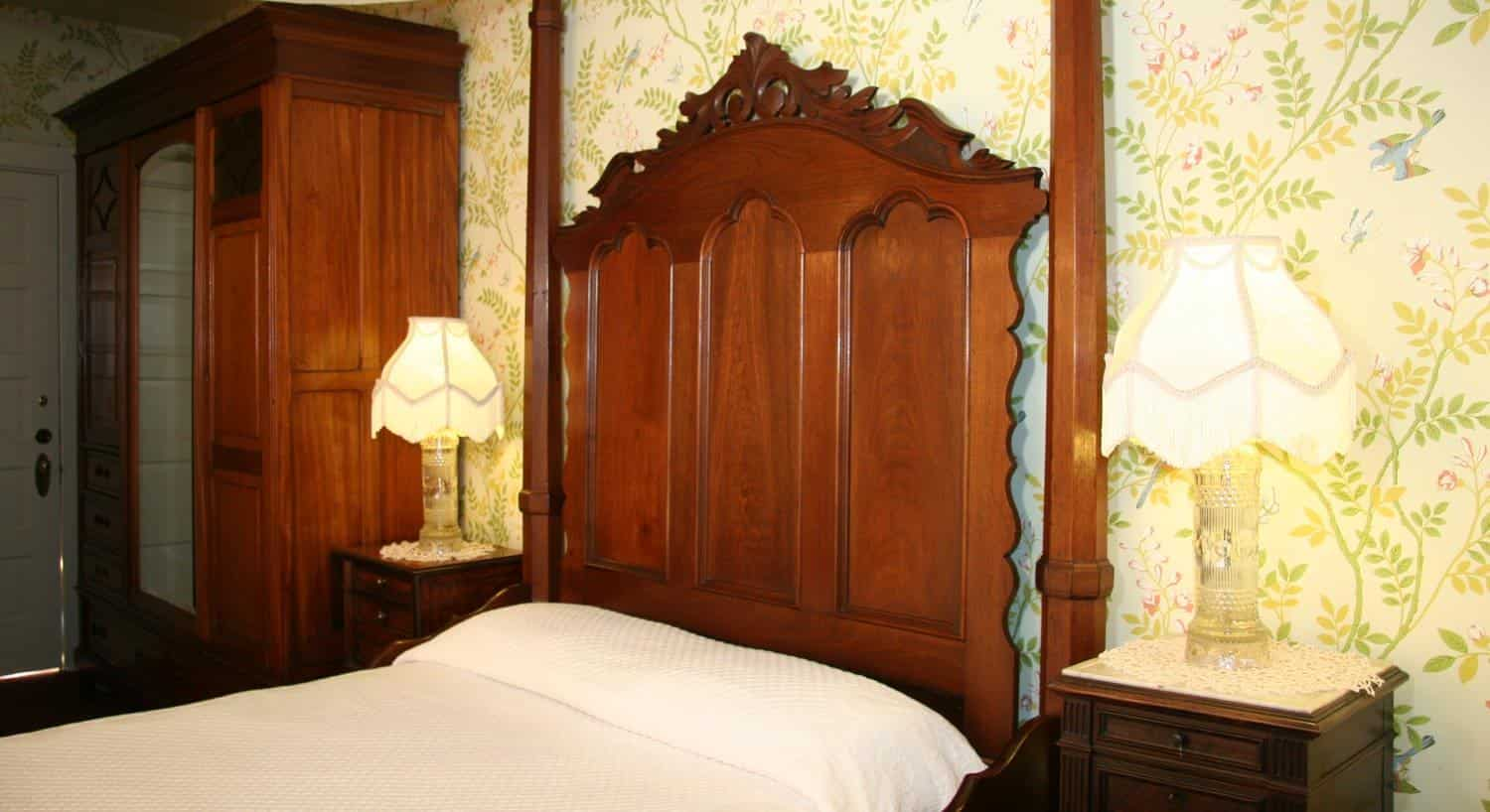 Garden guest room with leafy printed wallpaper, tall carved headboard, two nightstands and mirrored armoire