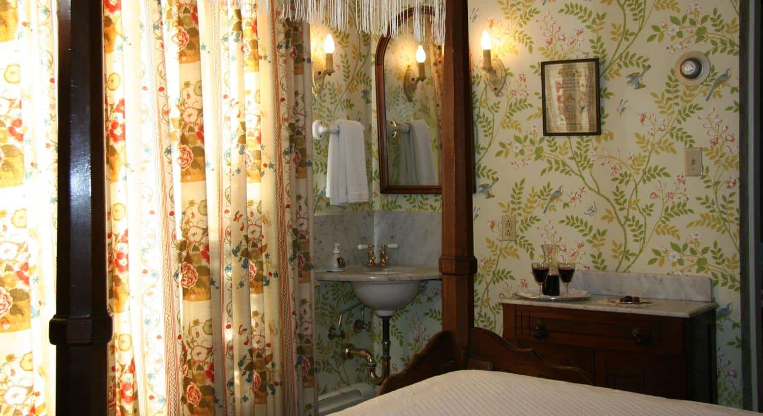 Garden guest room with leafy printed wallpaper, corner washbasin with mirror and canopy bed